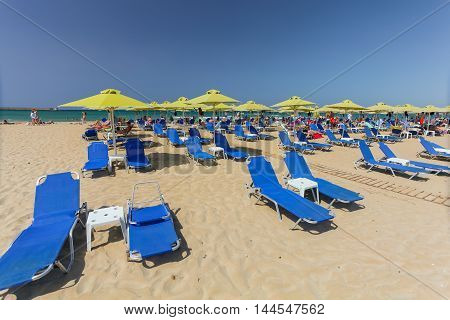 Rethymno, Island Crete, Greece, - July 1, 2016: City beach with people and blue daybeds with green umbrellas