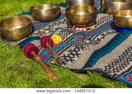 Singing bowls for massage in a row on grass