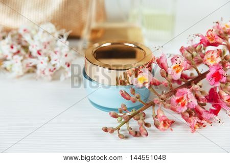 There White and Pink  Branches of Chestnut Tree,Blue Bottle Cream with Gold Cover are on White Table,Selective Focus