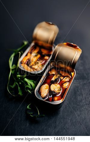 Open tin can with conserve food over black background. Mussels tin appetizer close up