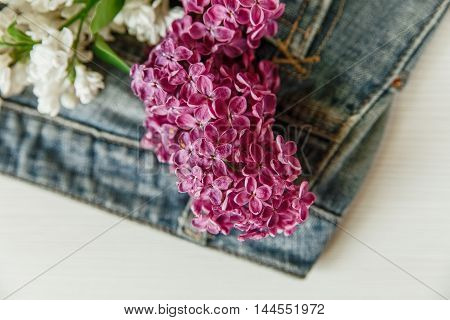 Two Branches of White and Purple Lilac in the Jeans Pocket.Selective Focus