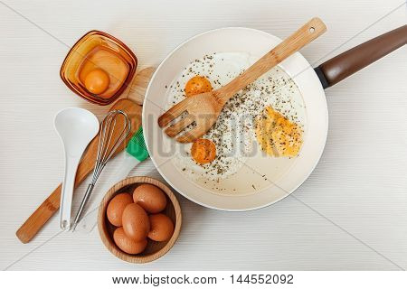 Fried eggs in the frying pan,breakfast ingredients,kitchen accessories.Fresh Brown Eggs in the Wooden Plate.Cooking morning food.White table