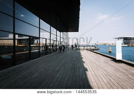 Copenhagen pier with wooden walkway and sea infrastructure at sunny day, Denmark.