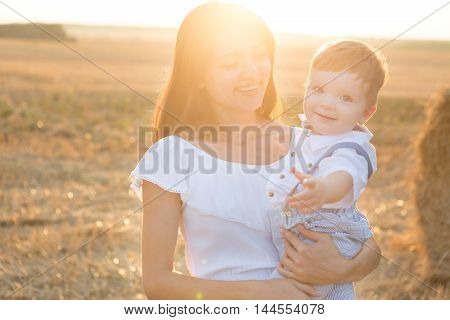 Happy Mother And Her Little Son In The Field.