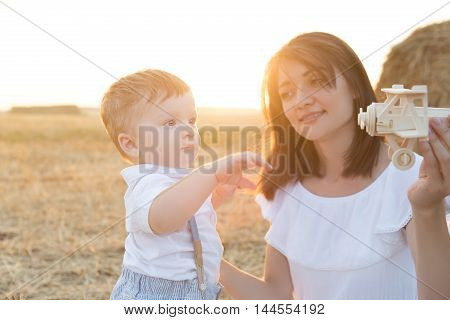 Mother And Her Child Playing In Field With Toy Airplane.