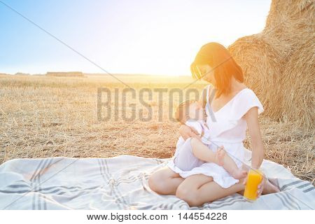Beautiful Happy Mother Breastfeeding Her Baby Boy Outdoor.