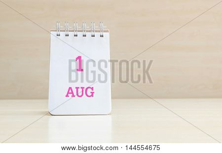 Closeup surface note book with pink 1 aug word in page on blurred brown wood desk and wood wall textured background with copy space under window light