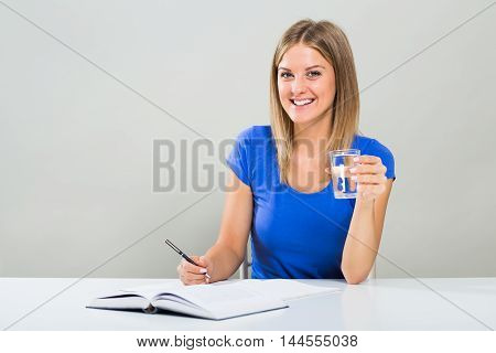 Beautiful female student is holding glass of water while studying.