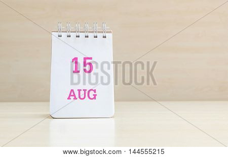 Closeup surface note book with pink 15 aug word in page on blurred brown wood desk and wood wall textured background with copy space under window light