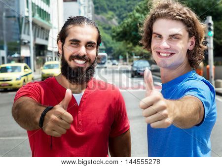 Happy caucasian guy with arabian friend showing thumb in the city