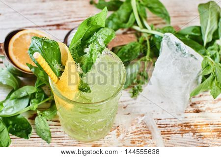 Alcoholic cocktail Basil smash in a glass beaker and a piece of ice on a wooden table