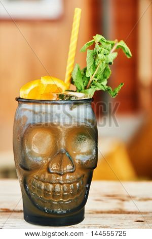 Alcoholic Mai tai cocktail with homemade spiced rum and almond syrup with the lime juice in a glass beaker in the shape of skulls and lemon on a wooden table