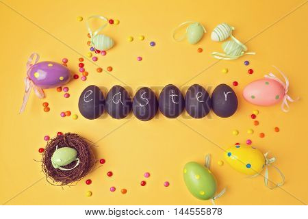 Easter decorations on yellow background. Papier-mache eggs painted with chalkboard paint. View from above.