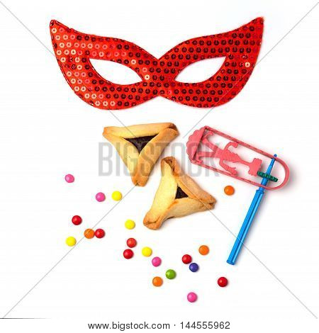 Hamantaschen cookies grogger and carnival mask on white background