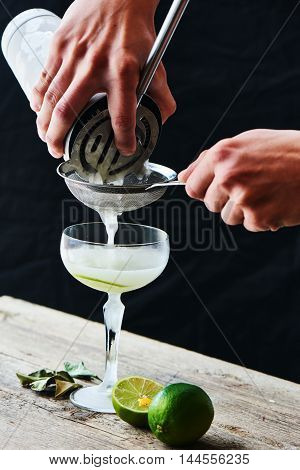 Hands pour through a sieve into a glass cocktail Daiquiri on a wooden table on black background