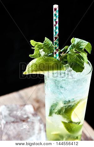 Alcoholic cocktail Mojito in a glass closeup on a wooden table
