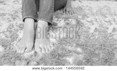 Closeup foot of asian woman sitting on gray carpet floor textured background in house in black and white tone