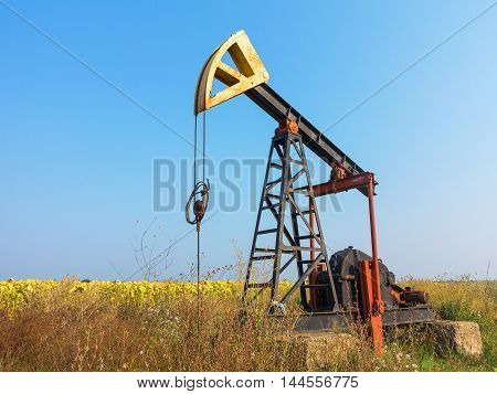 A Small Private Oil Derrick Pumps Oil On The Field. The Old Handicraft Oil Rig In The Background Of