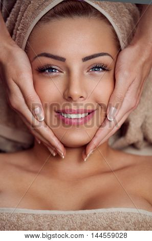 Spa woman, close-up of a young woman getting spa treatment, face massage