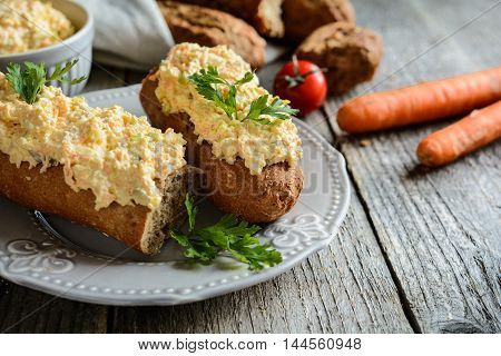 Curd Spread With Eggs, Carrot, Green Onion, Pickled Cucumber And Mayonnaise On A Whole Wheat Baguett