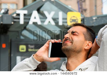 man feeling bad becouse he having a problem to order taxi from his cell phone