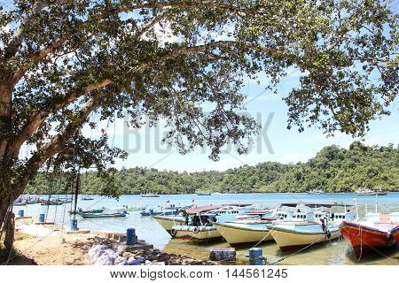 Sendang biru beach in the southern part of Malang, east java indonesia with long tail boat, sail boat, and yacht