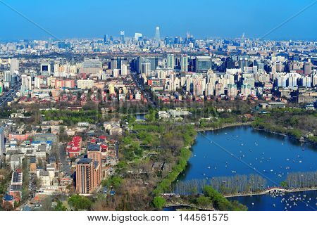 Beijing city aerial view with urban buildings and lake.