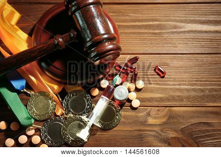 Syringe with pills, medals and gavel. Doping in sport concept