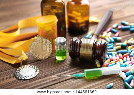 Syringe with pills, medal and gavel. Doping in sport concept