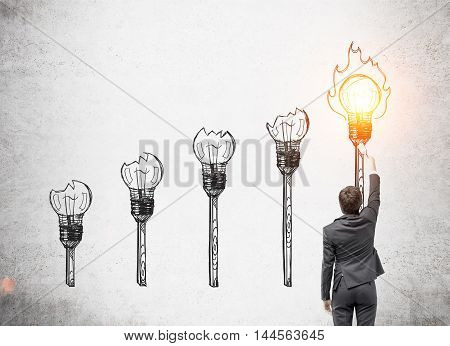 Man in suit lightning torch with light bulb. Concrete wall background. Concept of knowledge spreading.