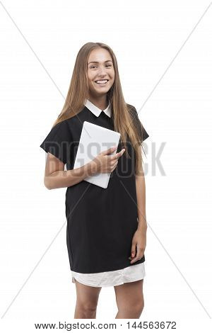 Smiling blond girl in black and white dress standing against white background. Isolated. Concept of young designer