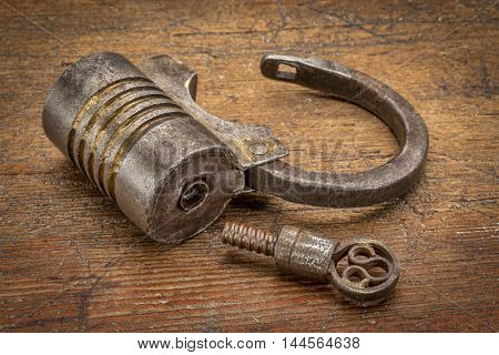 Vintage round shape hand crafted screw type iron padlock (unlocked) with a key on rustic wood