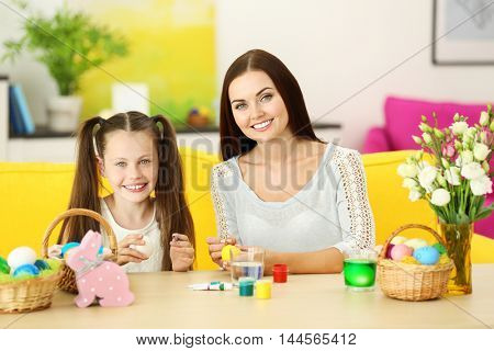 Mother and daughter painting eggs at Easter eve