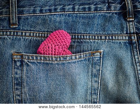Red knitted heart in the back pocket of jeans full frame