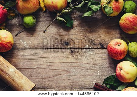 Autumn background: border from apples, pears and walnuts on old wooden table. Fall, Thanksgiving day and baking concept. Food frame, food background with copy space for text
