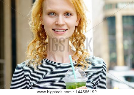 Closeup outdoors portrait of young attractive blue-eyed woman with cold refreshing drink