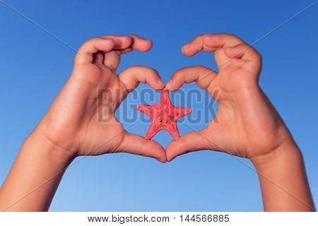 Child holds hands up to sky in the shape of a heart with starfish. Love shape child hands with starfish. Summer background.