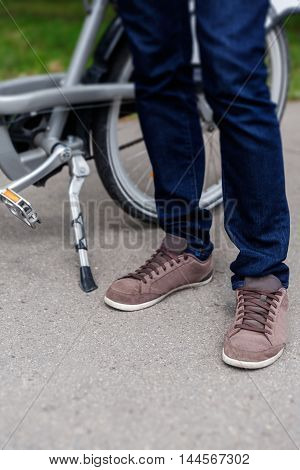 Guy in blue jeans and brown sneakers standing next to bicycle on the road