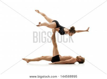 Studio photo of couple practising acrobatics. Isolated on white background