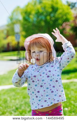 Cute little girl gets dandelion and smiling, happy family having fun and playing outdoor, summer nature