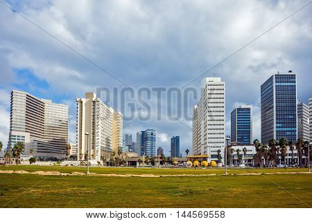 TEL AVIV, ISRAEL - JANUARY 1, 2016: Skyscrapers on Tel Aviv's seafront. Strong winds and bright sunshine - perfect weather for a winter walk
