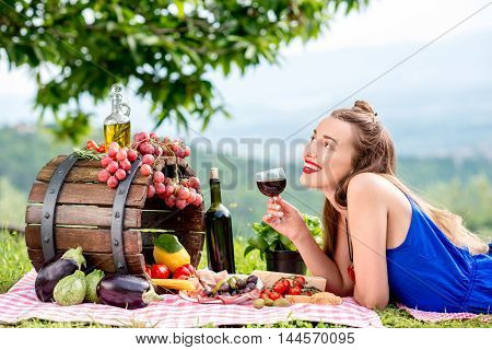 Beautiful woman lying on the grass with lots of tasty italian food and wine in the countryside in Tuscany.