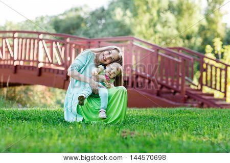 mom gently hugs small daughter in park next bridge