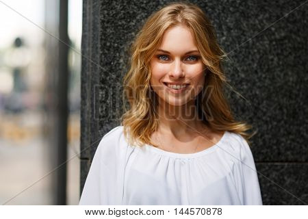 Outdoors portrait of cheerful smiling young beautiful blond woman looking at camera