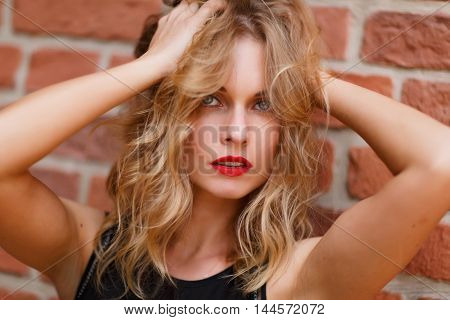 Portrait of attractive young blonde woman with red lips touching her hair against brick wall. Shoot on fast aperture