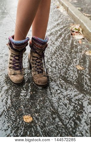 Female feet in high boots standing in a puddle in the rain close-up