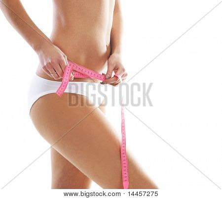 Young and sexy woman measuring her waist isolated over white background