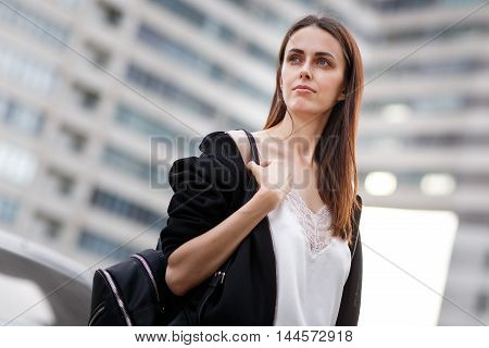 Closeup portrait of young brunette student with backpack one background of the building