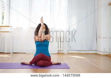 Brunette woman sitting on floor indoors and performing yoga asana