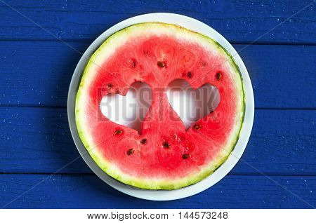 Round watermelon slice with cut in the shape of heart in plate on dark blue wooden table top view